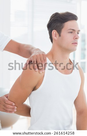Doctor stretching a young man arm in medical office