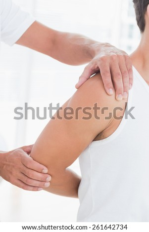 Doctor stretching a young man arm in medical office - stock photo