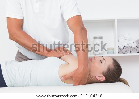 Doctor stretching a young woman back in medical office - stock photo
