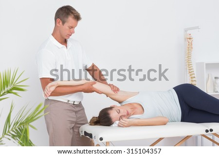 Doctor stretching his patient arm in medical office