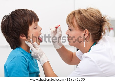 Doctor taking saliva sample from little boy - childhood infectious diseases - stock photo