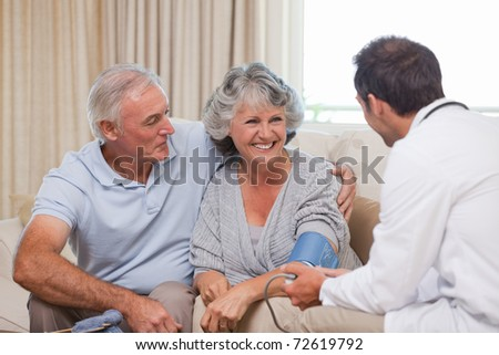 Doctor taking the blood pressure of his patient - stock photo