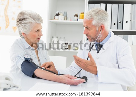 Doctor taking the blood pressure of his retired patient in the medical office - stock photo