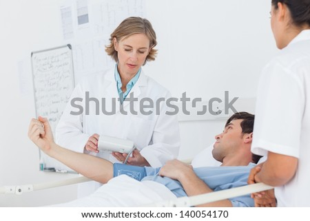 Doctor taking the blood pressure of male patient in hospital - stock photo