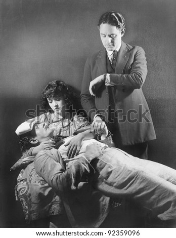 Doctor taking the pulse of a sick man