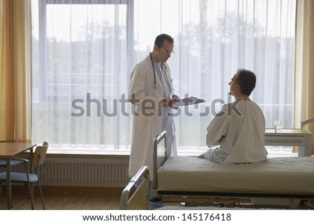 Doctor talking to a male patient in hospital room - stock photo