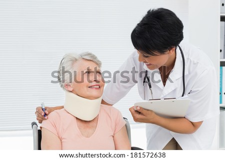 Doctor talking to a senior patient with cervical collar at the hospital