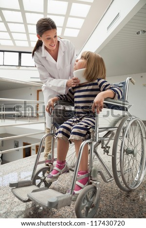 Doctor talking to chld with neck brace in wheelchair in hospital corridor - stock photo
