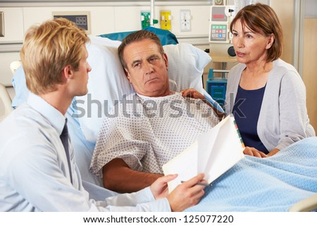 Doctor Talking To Couple On Ward - stock photo