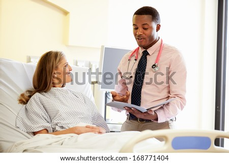 Doctor Talking To Female Patient In Hospital Room - stock photo
