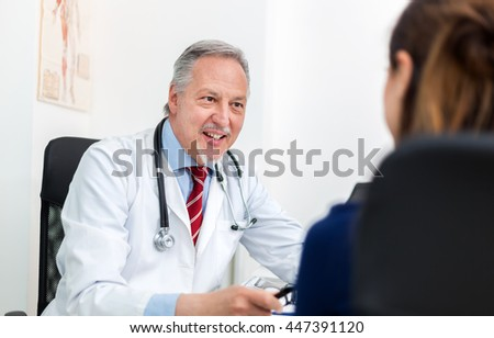 Doctor talking to his patient in his office - stock photo