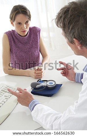 Doctor talking to his young female  patient at the office  - stock photo