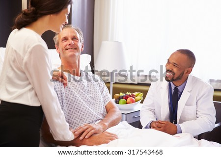 Doctor Talking To Male Patient And Wife In Hospital Bed - stock photo