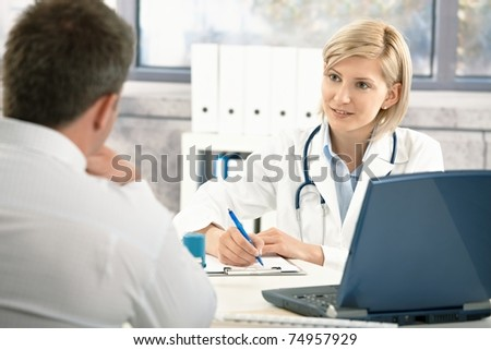 Doctor talking to patient in office, taking notes, smiling.? - stock photo