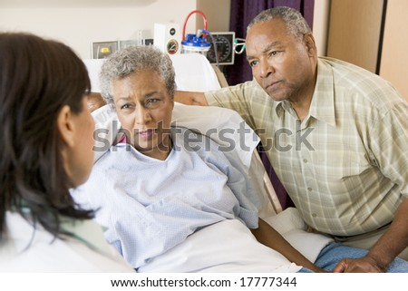 Doctor Talking To Senior Couple - stock photo