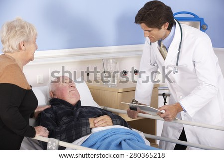 Doctor talking to senior couple in hospital - stock photo