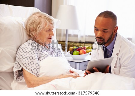 Doctor Talking To Senior Female Patient In Hospital Bed - stock photo