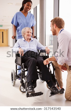 Doctor Talking To Senior Female Patient In Wheelchair