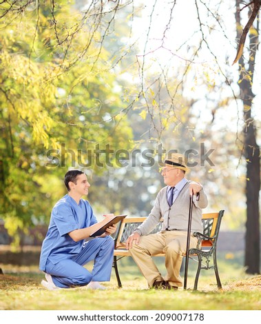 Doctor talking to senior gentleman in park shot with tilt and shift lens - stock photo