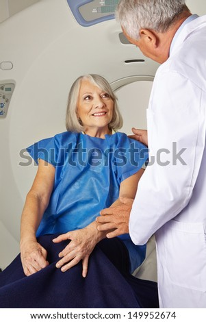 Doctor talking to senior patient at MRI machine in hospital