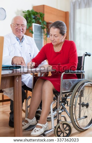 doctor talking to woman in wheelchair.