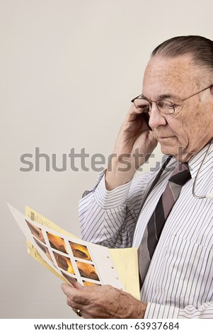 doctor talks on cell phone as he looks at results of colon test. - stock photo