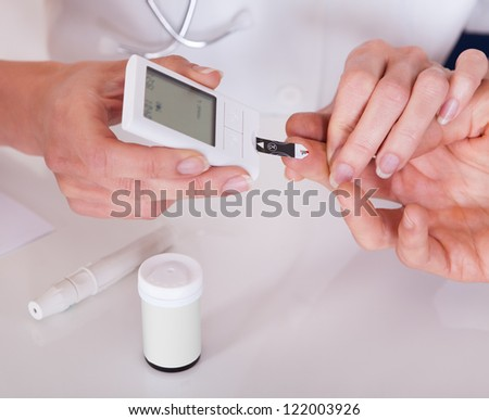 Doctor testing a patients glucose level after pricking his finger to draw a drop of blood and then using a digital glucometer