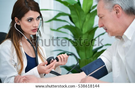 Doctor testing blood pressure to a senior patient