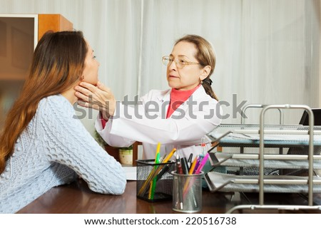 Doctor touching gland of young female patient - stock photo
