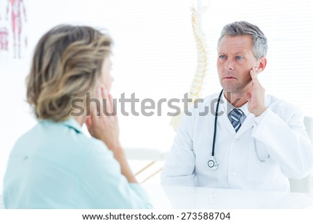 Doctor touching his jaw in medical office
