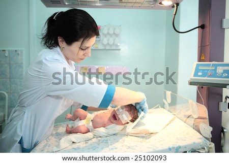doctor  treat newborn baby in hospital - stock photo