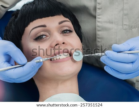 Doctor treats teeth. Dentist makes the process of treatment of a beautiful young girl. - stock photo