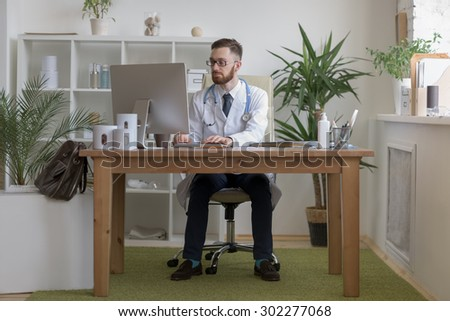 Doctor typing on his computer in the office - stock photo