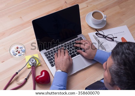 Doctor using a laptop, sitting at his desk - stock photo