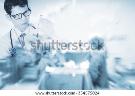 Doctor using a syringe on blurred background with team surgeon in operating room  , concept for healthcare and medicine - stock photo
