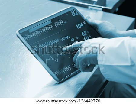 Doctor Using Digital Tablet with medical parameters - stock photo