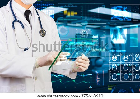 doctor using hi-tech transparency tablet  in operating room - stock photo