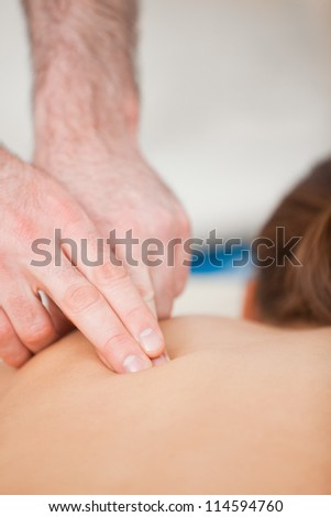 Doctor using his finger to massaged the back of his patient in a room - stock photo