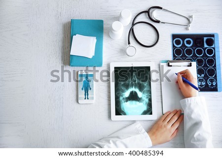 Doctor using his tablet-pc, close up - stock photo