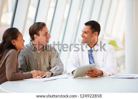 Doctor Using Tablet Computer Discussing Treatment With Patients - stock photo