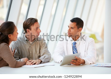 Doctor Using Tablet Computer Discussing Treatment With Patients