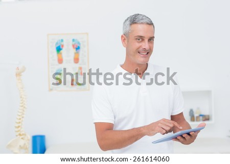 Doctor using tablet pc in medical office - stock photo