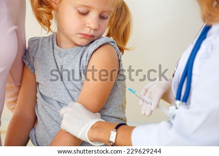 Doctor vaccinating small redhead girl.
