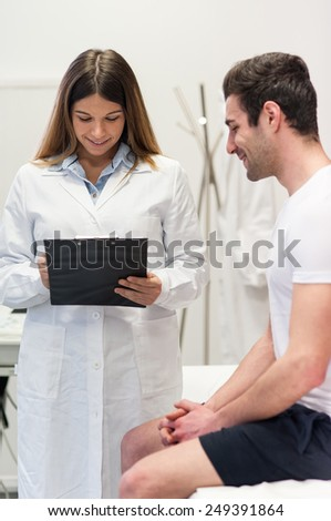 Doctor visiting her male patient and taking notes at office.