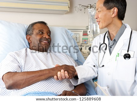 Doctor Visiting Senior Male Patient On Ward - stock photo
