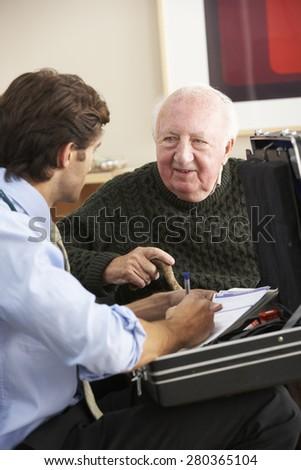 Doctor visiting senior man at home - stock photo