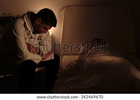 Doctor watching over his young patient with cancer - stock photo