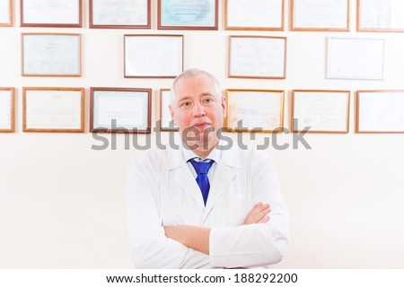 doctor white coat, folded hands over office wall with certificate background - stock photo