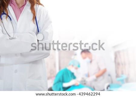 Doctor with a stethoscope with his team working in the background - stock photo
