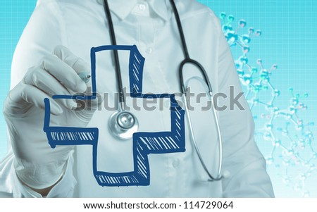 Doctor with a stethoscope writing first aid sign as medical concept - stock photo